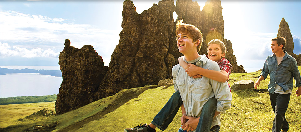 two boys and man on grassy mountain vantage point by rocks with beautiful water view